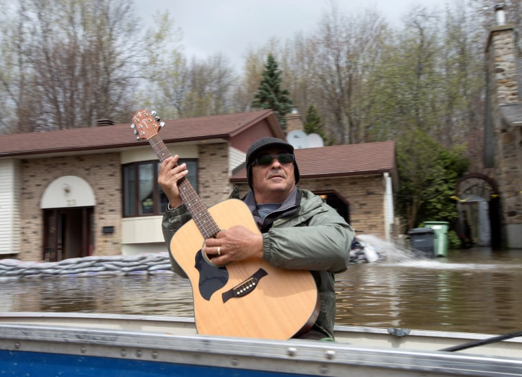 Image: A man plays his guitar as he travels in a boat to collect water supplies in a flooded residential neighbourhood in Ile Bizard
