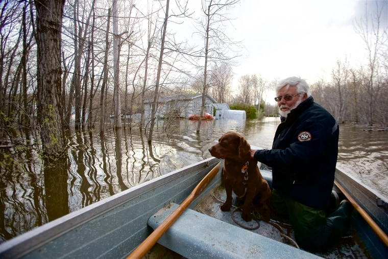 Image: Michel Guerard and his dog Choco return with their boat to help their neighbors evacuate