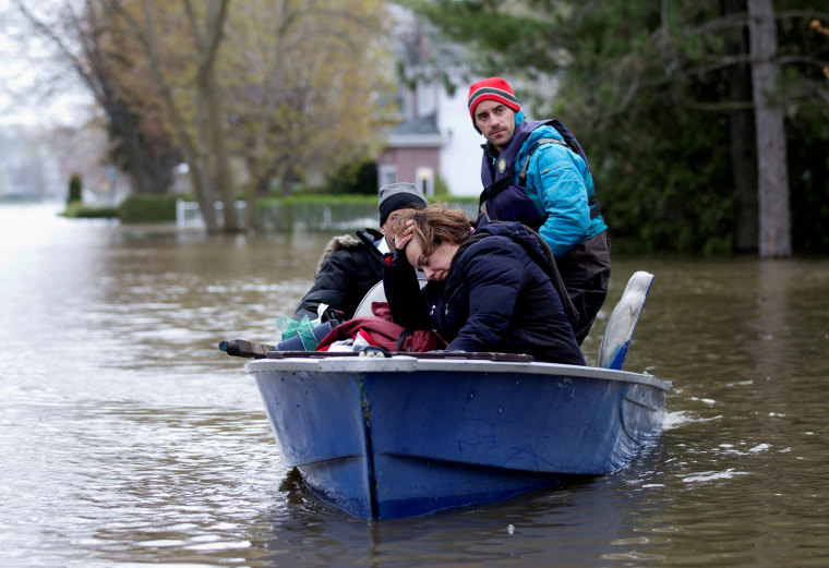 Image: Mina Tayarani is evacuated from her home in a flooded residential neighbourhood in Ile Bizard, Quebec, Canada