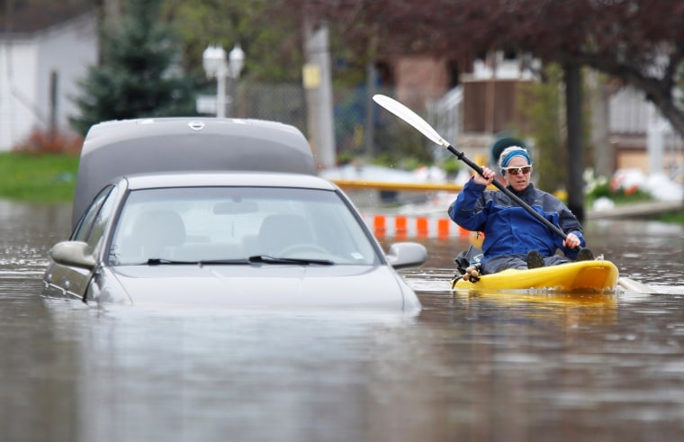 Image: A woman paddles a kayak past an abandoned car on a flooded residential street in Gatineau
