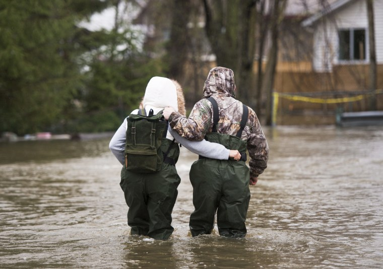 Image: A couple walks through the flooded streets in the Ile-Mercier district of Ile-Bizard, Quebec