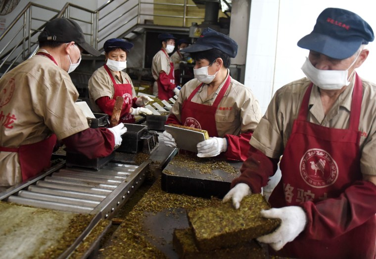 Image: Workers package bricks of tea leaves for export in Wuyi, China