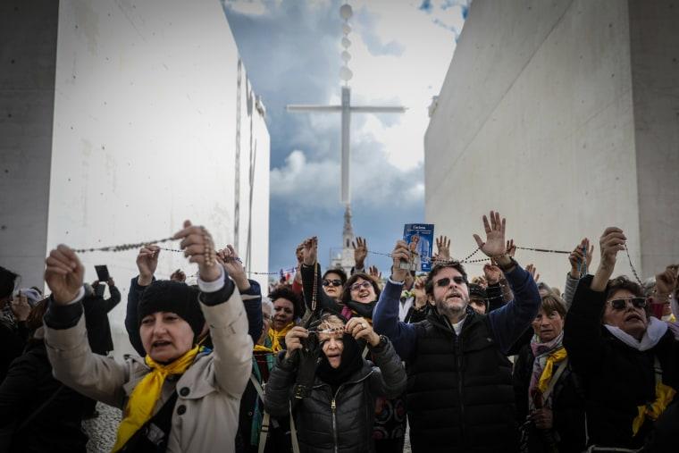 Image: Pilgrims pray at the Sanctuary of Fatima