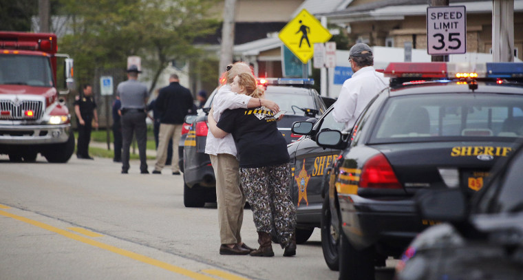 Image: People hug as emergency personnel arrive to the scene of a shooting outside Pine Kirk nursing home