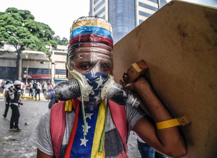 Image: A Venezuelan opposition activist wears a homemade gas mask