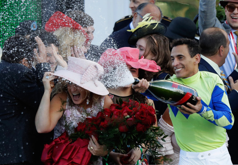 Image: Jockey John Velazquez sprays champagne in the winner's circle
