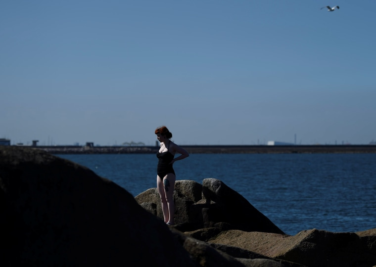 Image: A woman enjoys the good weather at the Forty Foot diving area and beach in Sandycove