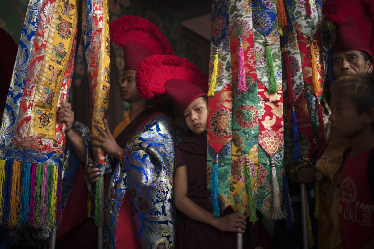 Image: A young Buddhist monk takes part in Buddha's birthday prayers