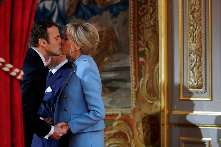 Image: French President Emmanuel Macron kisses his wife Brigitte Trogneux during the handover ceremony in Paris