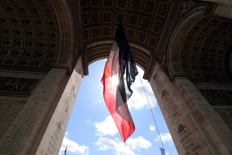 Image: A giant French flag hang fro the Arc de Triomphe in honour of President Emmanuel Macron attends a ceremony at the Tomb of the Unknown Soldier in Paris