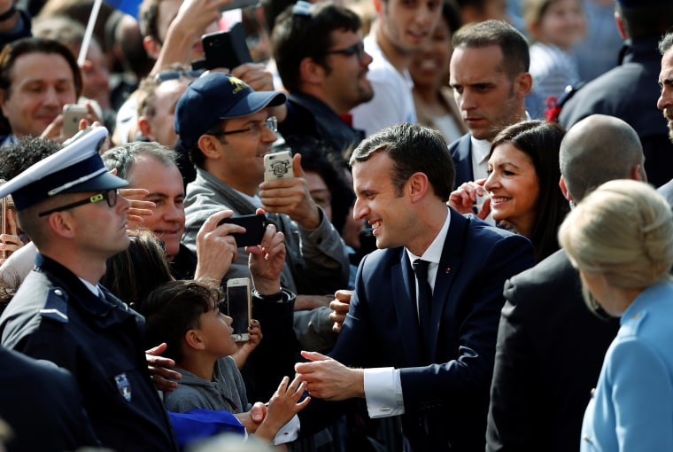 Image:  French President Emmanuel Macron, his wife Brigitte Trogneux and Paris Mayor Anne Hidalgo greet people in the crowd outside the Hotel de Ville in Paris