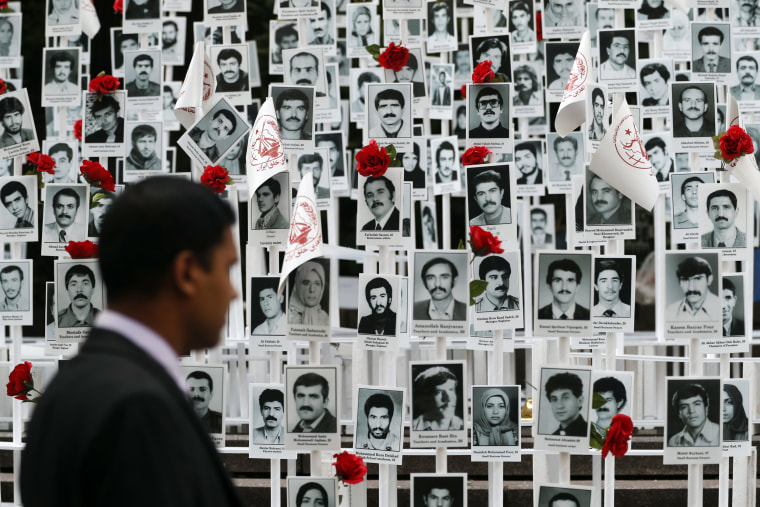 Image: A man looks at photos of some of the people executed in Iran during a rally outside the United Nations