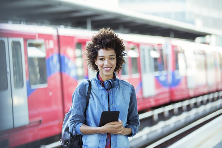Image: A woman smiles inside a train station