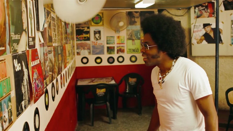 Alex Cuba in Cuban studio looking at albums on the wall