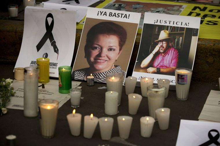 Candles burn in front of pictures of murdered journalists Miroslava Breach, left, and Javier Valdez during a demonstration against the killing of journalists, outside the Interior Ministry in Mexico City, Tuesday, May 16, 2017.