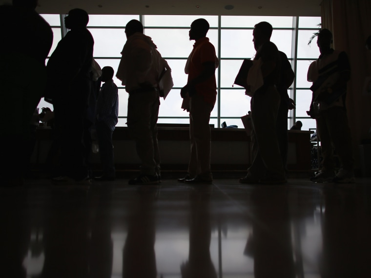 Image: People stand in line to apply for a job during a job fair in Miami