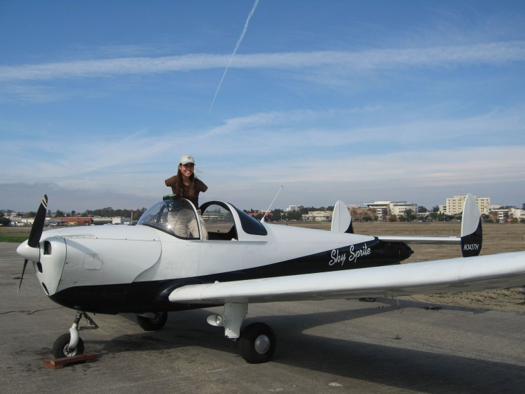 Jessica Cox stands in the cockpit of an Ercoupe aircraft.