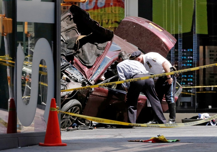 Image: Police investigate the vehicle that drove onto sidewalk and struck pedestrians in Times Square in New York