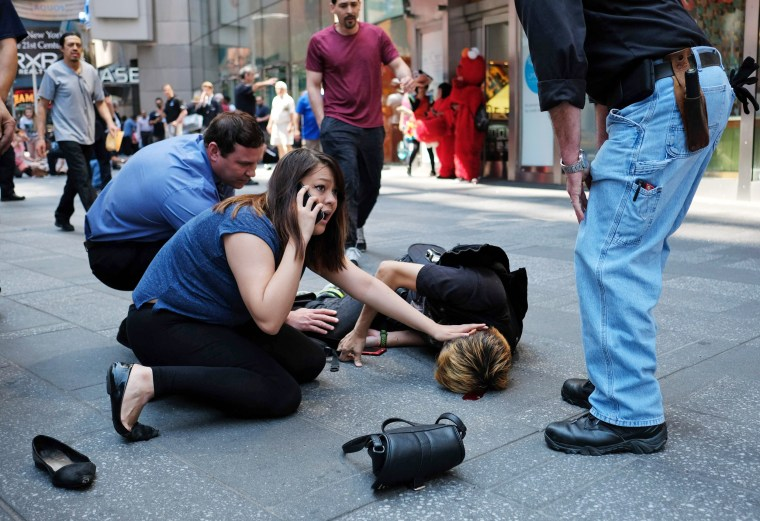 Image: People attend to an injured man after a car plunged into him in Times Square