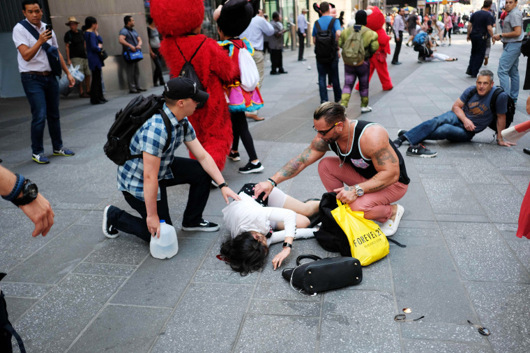 People attend injured pedestrians a moment after a car plunged into them in Times Square