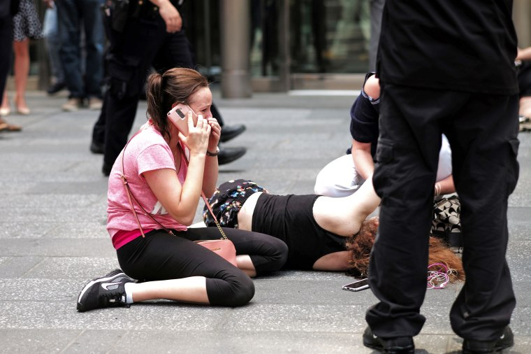 Image: A woman makes a phone call as others attend to an injured person after a car plunged into them in Times Squar