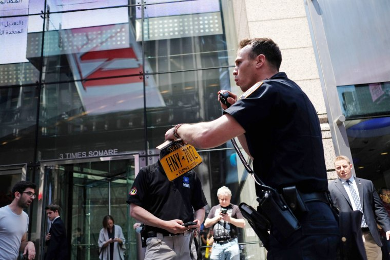 Image: A Police officer collects the license plate of a car after it plunged into pedestrians in Times Square