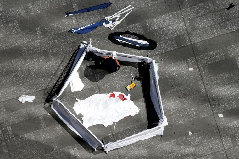 Image: A body of a deceased person lies covered on the sidewalk in front of the 3 Times Sq building in Times Square