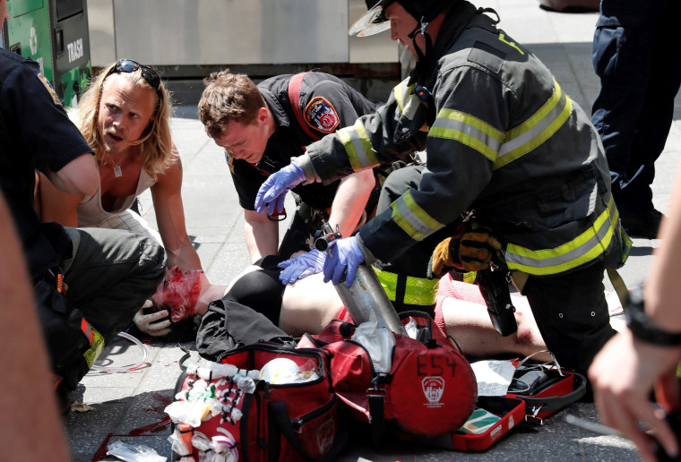 Image: An injured woman is helped by emergency workers as she lies on the sidewalk in Times Square