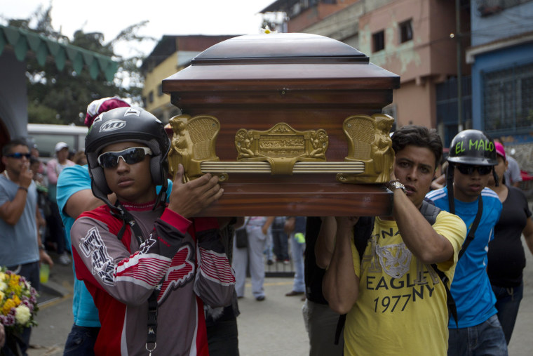 Image: Relatives of a crime victim carry his coffin as tribute prior his burial in Caracas