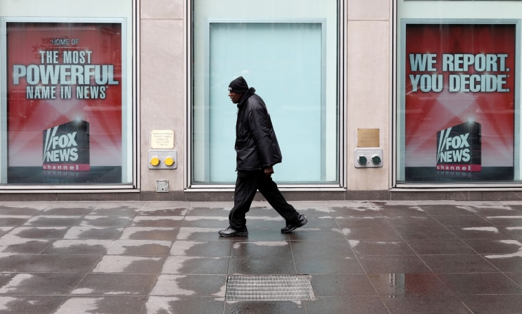 Image: A man walks past News Corporation Headquarters in New York