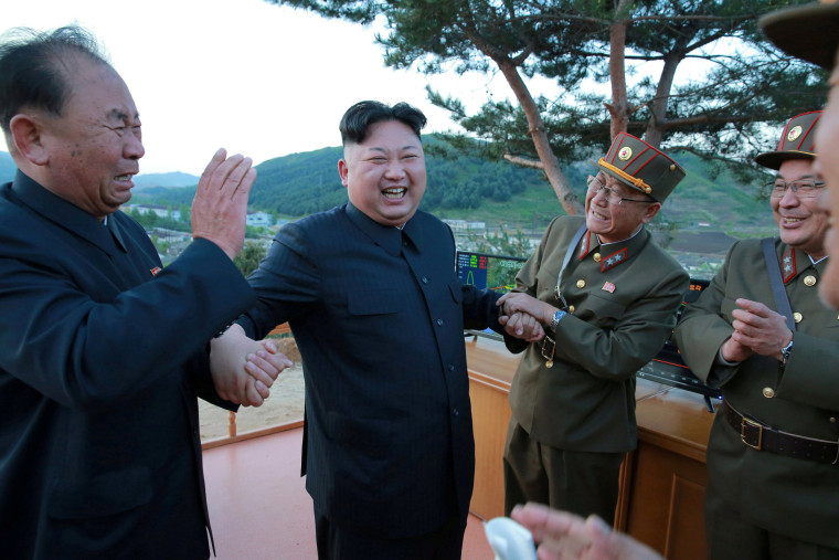 Image: North Korean leader Kim Jong Un reacts with members of the Korean People's Army scientists and engineers