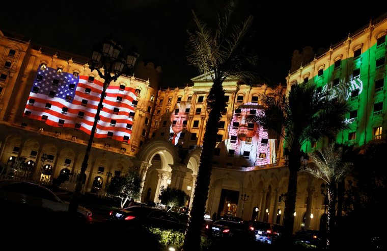 Image: Trump and Saudi Arabia's King Salman are projected on the front of the Ritz-Carlton, where Trump is staying in Riyadh