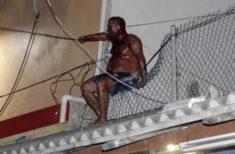 Image: A man sits covered in blood after an angry mob attacked him for reportedly insulting Mexicans
