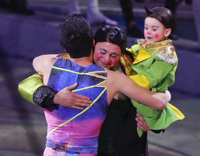 Image: Davis Vassallo, center, hugs a member of the trapeze troupe