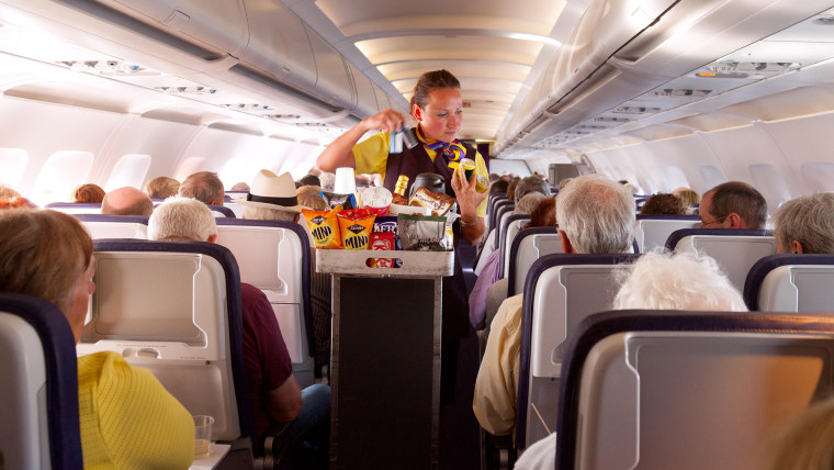 A flight attendant member of the cabin crew serving food on a Monarch Airlines airplane from Madeira to Gatwick airport, UK