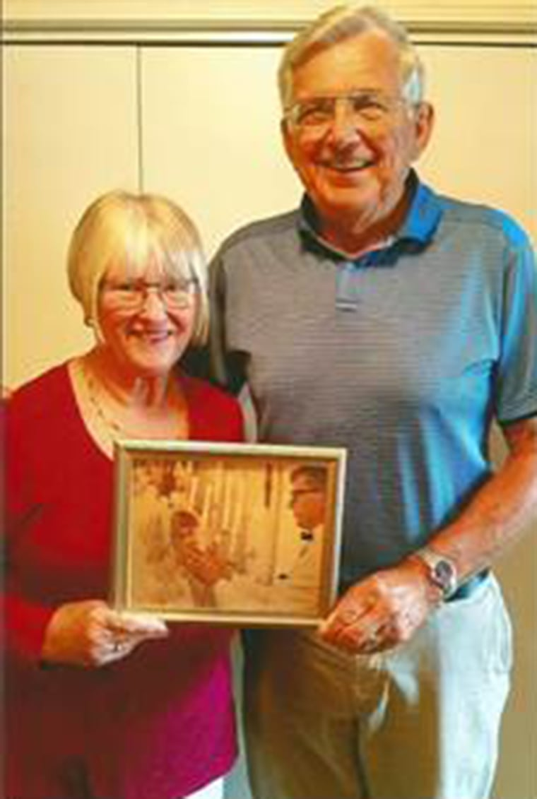 Mike and Carol Anderson holding a beloved photo of them on their wedding day, when his look deep into her eyes told her he loved her.