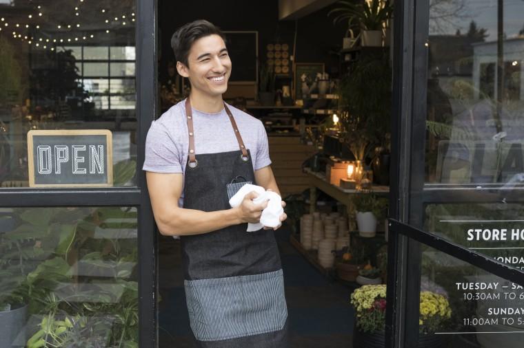 Smiling male shop owner looking away in doorway