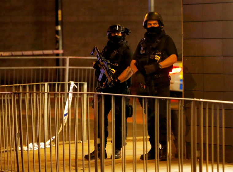 Image: Armed Police Stand Next to a Police Cordon Outside Manchester Arena
