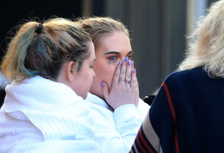 Image: Young victims, look visibly distressed as they leave the Park Inn hotel that took-in victims from the Manchester Arena stadium