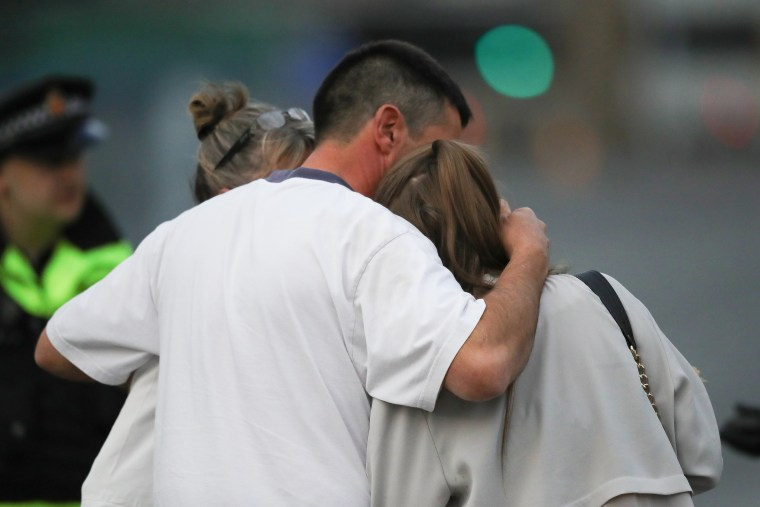 Image: A man embraces a woman and a teenager as he collects them from the Park Inn Hotel