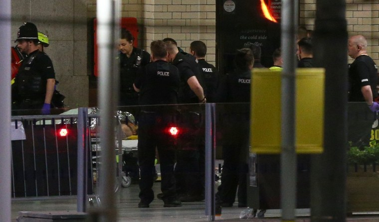 Image: A person is wheeled away on a stretcher at Victoria Railway Station close to the Manchester