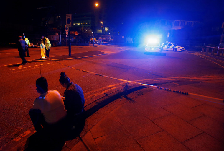 Image: People sit by the side of the road next to a police cordon outside the Manchester Arena
