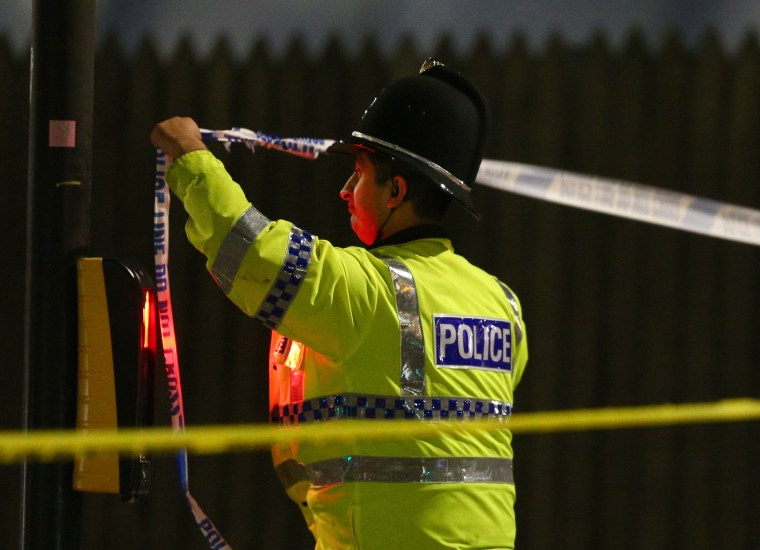 Image: A police officer ties police crime scene tape close to the Manchester Arena