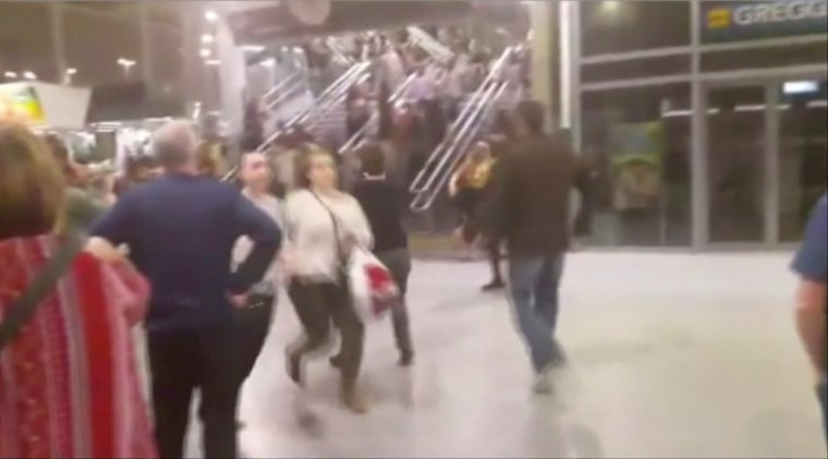 Image: People run down stairs as they try to leave the Manchester Arena