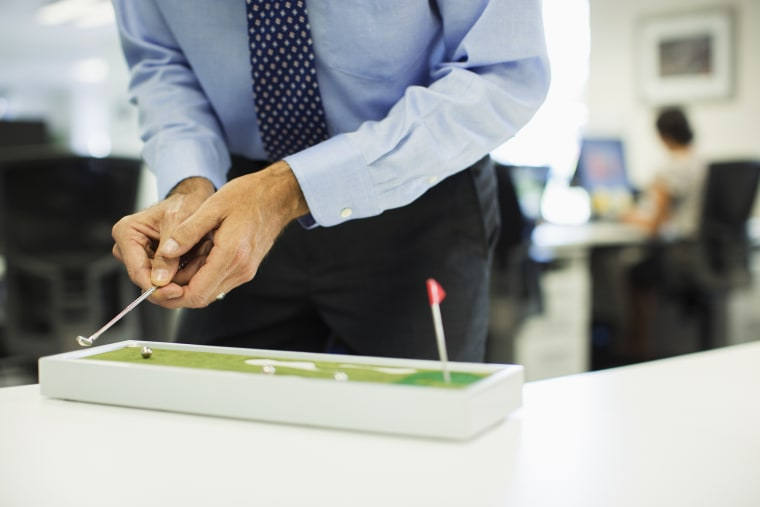 Image: A businessman plays with a toy golf set in the office