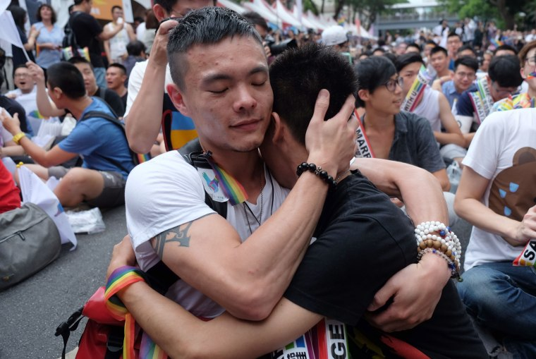 Image: Crowds hugged and wept outside the parliament in Taipei after Taiwan's gay marriage ruling.