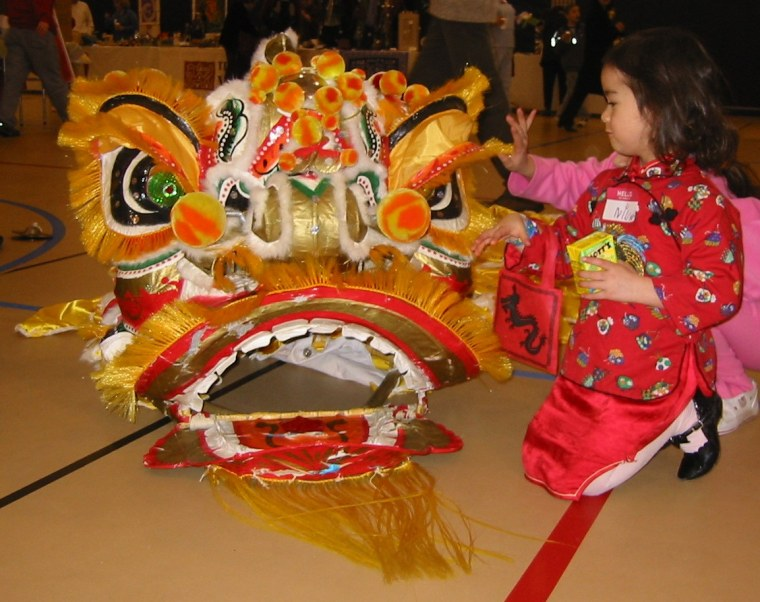 Frances Kai-Hwa Wang's daughter meeting a Chinese lion up close for the first time at a Chinese New Year's cultural event