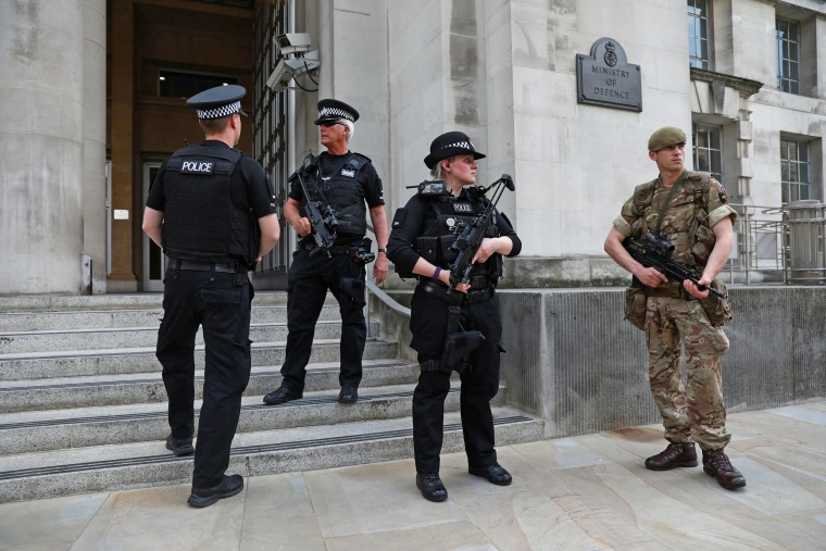 Image: A soldier and police officers stand outside the Ministry of Defence in London