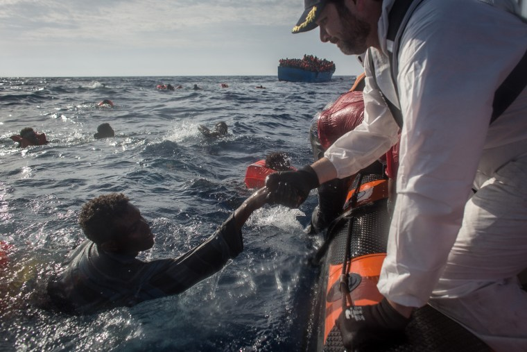 Image: Crew on the Migrant Offshore Aid Station (MOAS) vessel 'Phoenix' help a man bound for Italy, Wednesday.