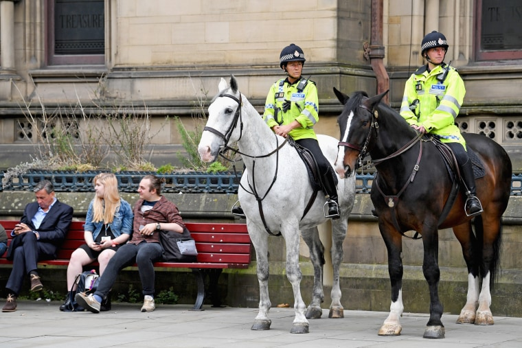 Image: Mounted Police patrol as members of the public lay floral tributes and messages in Manchester